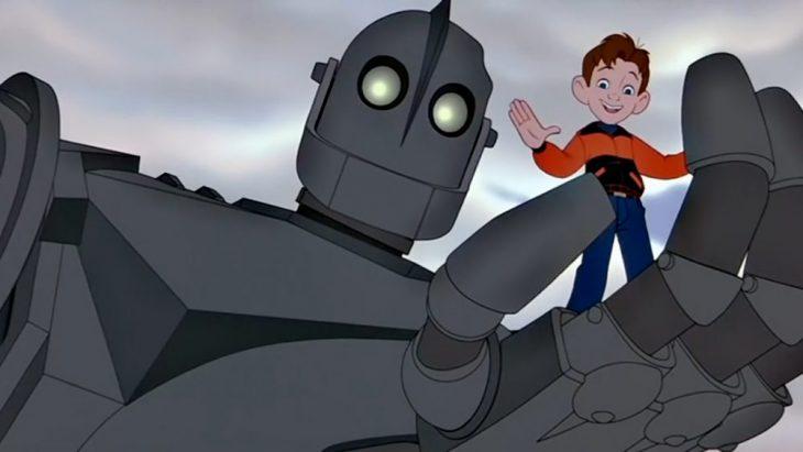 Dibujo animado de un robot de hierro sujetando a un niño en la palma de su mano, escena de la película El gigante de hierro