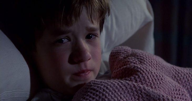 Niño recostado en su cama, cubriéndose con una manta de color rosa tejida, escena de la película El sexto sentido, Haley Joel Osment