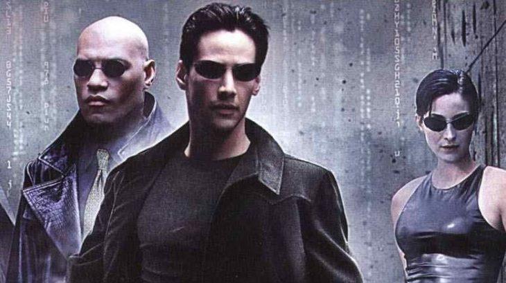 Grupo de personas usando gafas y ropa oscuras, bajo la lluvia, escena de la película Matrix, Keanu Reeves, Carrie-Anne Moss, Laurence Fishburne