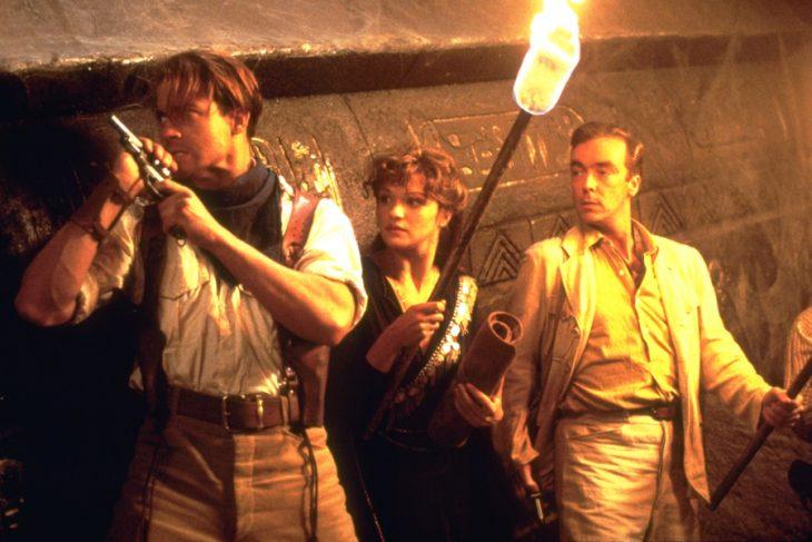 Grupo de personas recargadas en una pared con jeroglificos, sosteniendo antorchas, escena de la película La Momia, Rachel Weisz, Brendan Fraser, John Hannah