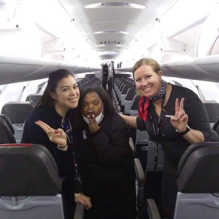 Shantell Pooser, azafatas dentro de un avión de American Airlines, haciendo señal de amor y paz, sonriendo para una fotografía del recuerdo