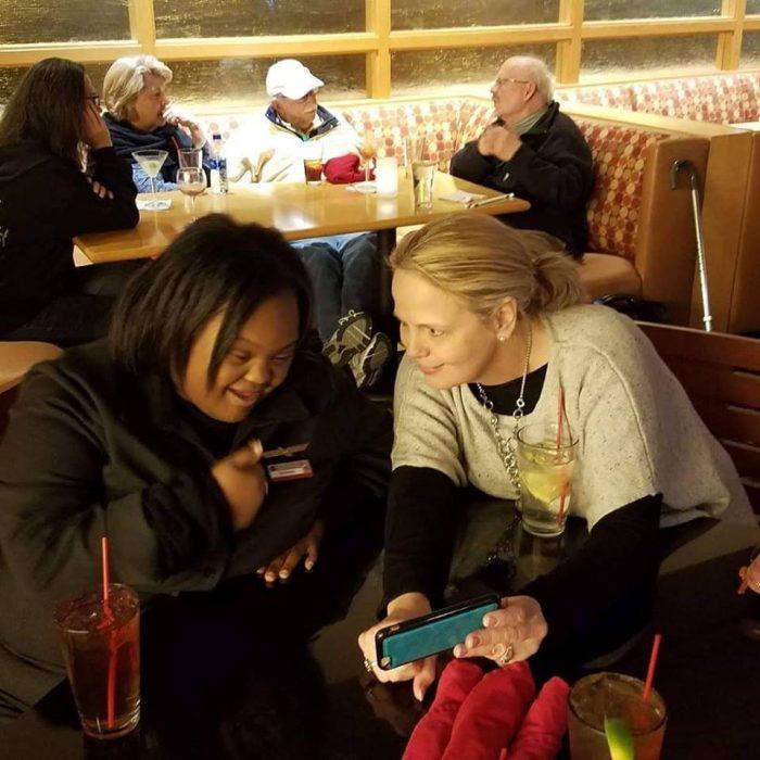 Shantell Pooser , mujeres en una sala de espera en un comedor de aeropuesto, mirando la tablet, antes de volar en American Airlines