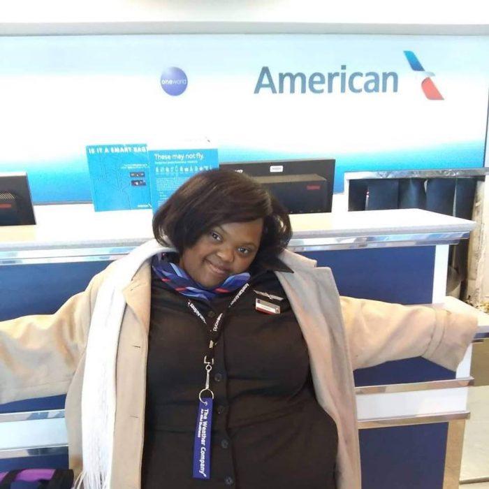 Shantell Pooser vestida de azafata, recargada en un mostrador de documentación del aeropuerto, mirando hacia la cámara y sonriendo