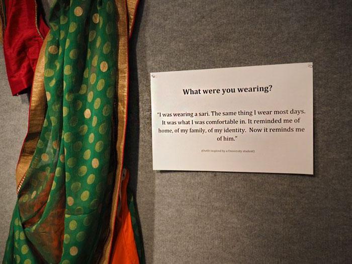 Sari expuesto en una galería de arte junto a la leyenda de la historia que sufrió una victima de abuso cuando lo estaba usando