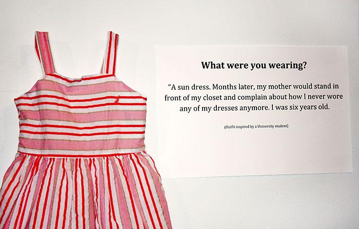 Cartelón que muestra el vestido que usó una victima de abuso cuando era una niña