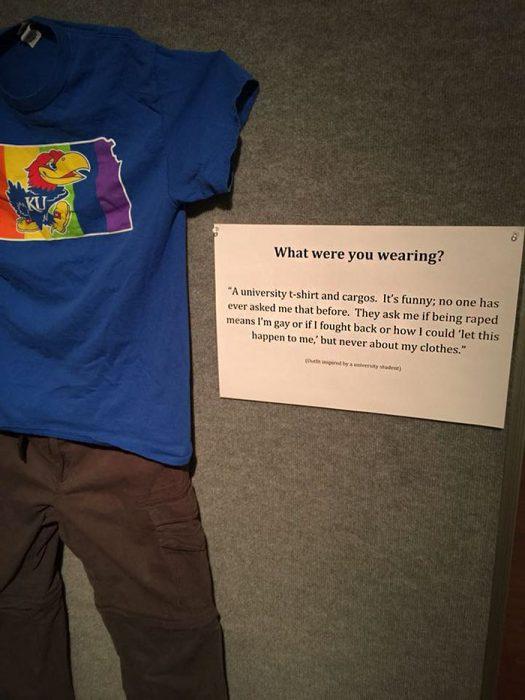 Camisa azul de una universidad y pantalones color café expuestos en una galería de arte