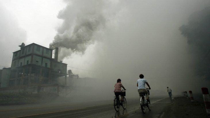 Boys pass by bicycle near a factory with polluting waste