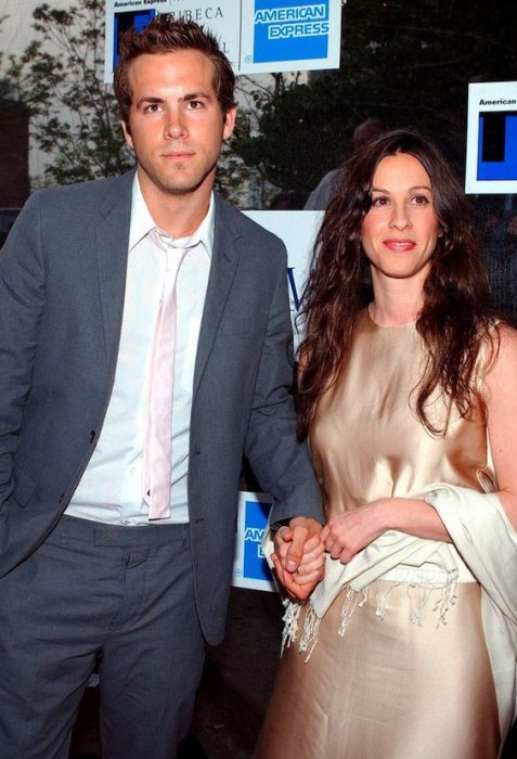 Ryan Reinolds and Alanis Morissette holding hands in awards