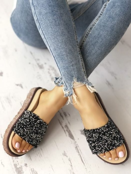 Feet of a girl wearing jeans and black sandals with sparkles
