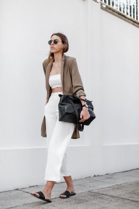 Girl wearing a white outfit with a brown cardigan, black bag and black sandals while walking down the street