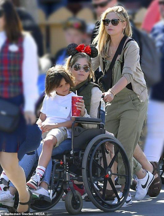 La actriz Sarah Michelle Gellar empujando la silla de ruedas de la actriz Selma Blair en Disneylandia mientras carga a su hijo