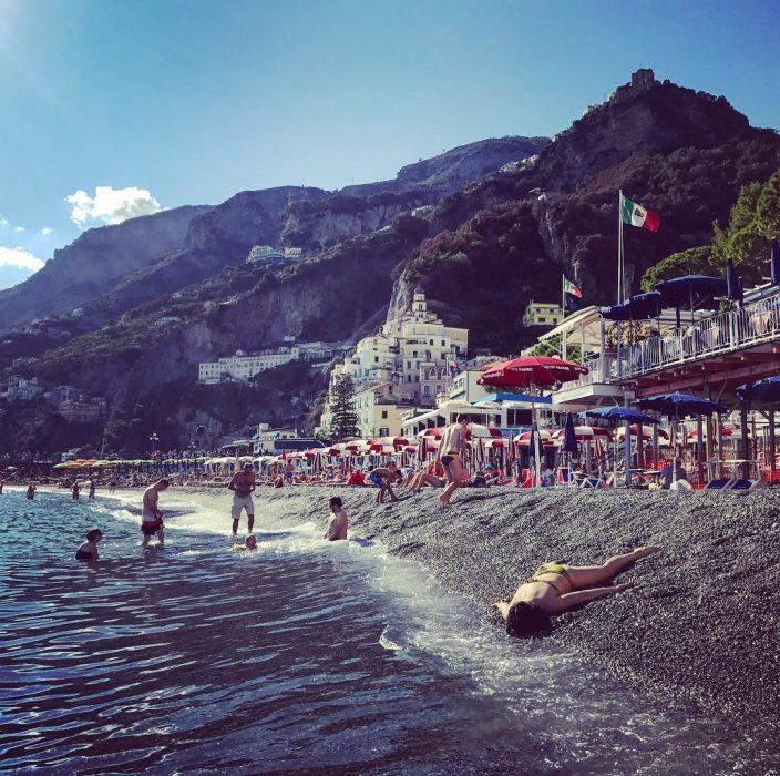 STEFDIES, la chica que se ha vuelto viral por sus antiselfies, selfie de mujer en la costa junto al mar en playa Amalfitana en Italia, con montañas en el fondo y turistas