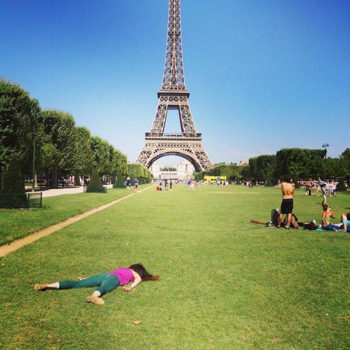 STEFDIES, la chica que se ha vuelto viral por sus antiselfies, selfie de mujer con clusa rosa frente a la Torre Eiffel con turistas alrededor en el pasto