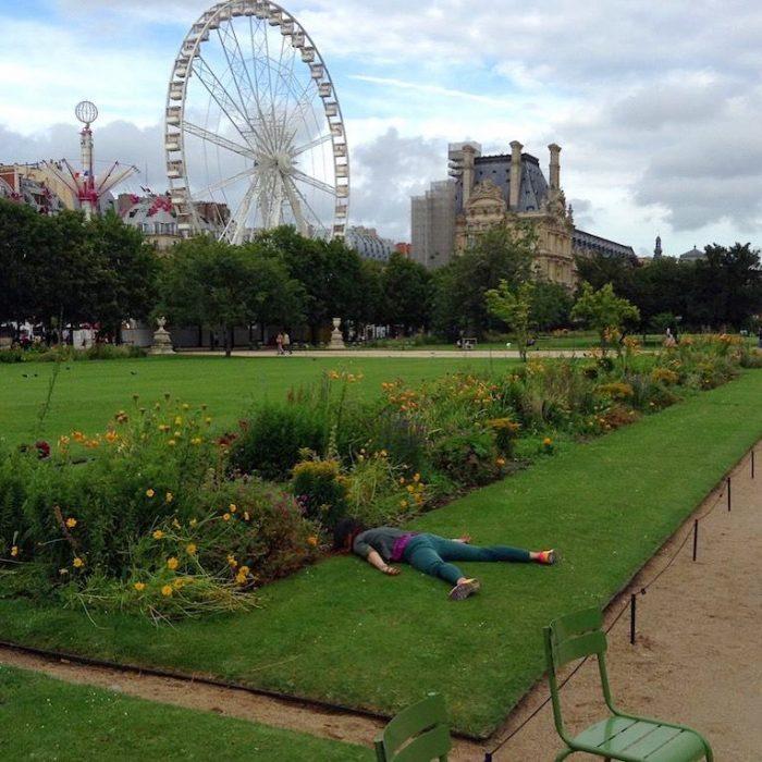 STEFDIES, la chica que se ha vuelto viral por sus antiselfies, selfie de chica en jardín de las Tullerías en París, Francia, en un jardín con flores frente a una montaña rusa