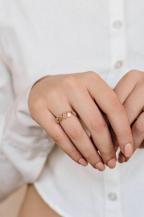 Mujer mostrando sus manos delgadas que portan un anillo dorado con piedras colgantes