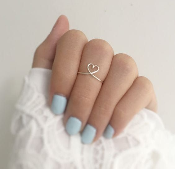 Woman showing her hand with nails in blue tone and heart-shaped ring in center