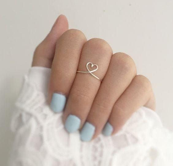 Mujer mostrando su mano con uñas en tono azul y anillo en forma de corazón al centro