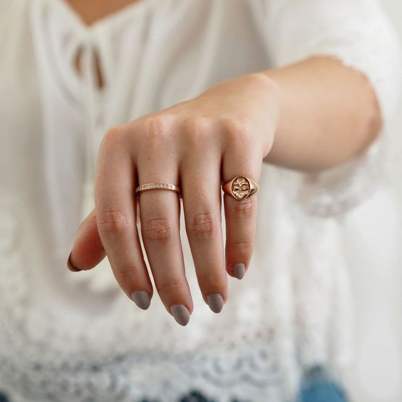 Woman showing her left hand holding small golden rings on the little finger and a half