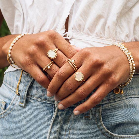 Manos de mujer con anillos y pulseras doradas