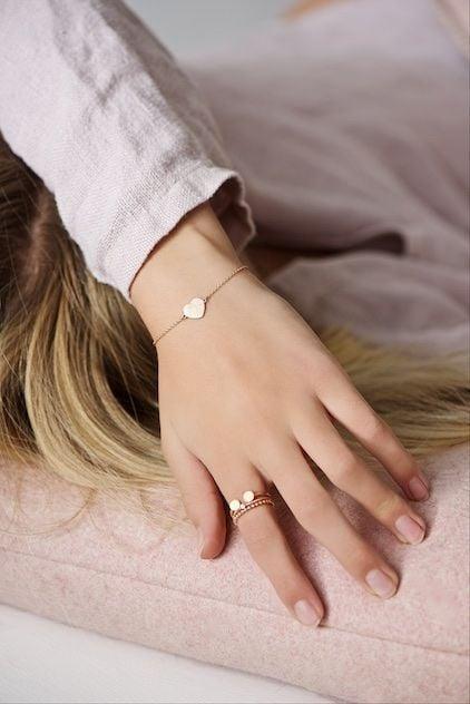Chica recostada sobre una cama cubriendo su rostro con su brazo izquierdo mostrando su anillo en el dedo índice