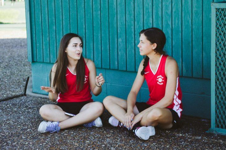 Tipo de amiga Cáncer, par de amigas sentadas en el asfalto platicando sobre un partido de fútbol