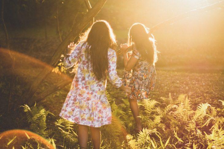Tipo de amiga Capricornio, chicas con vestidos floreados corriendo por el campo a manera de juego mientras se divierten con sus amigas