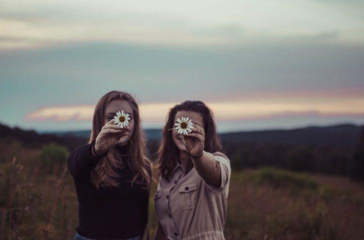 Tipo de amiga Acuario, chicas a mitad del campo en pleno atardecer sosteniendo un par de margaritas en sus manos mientras las fotografían