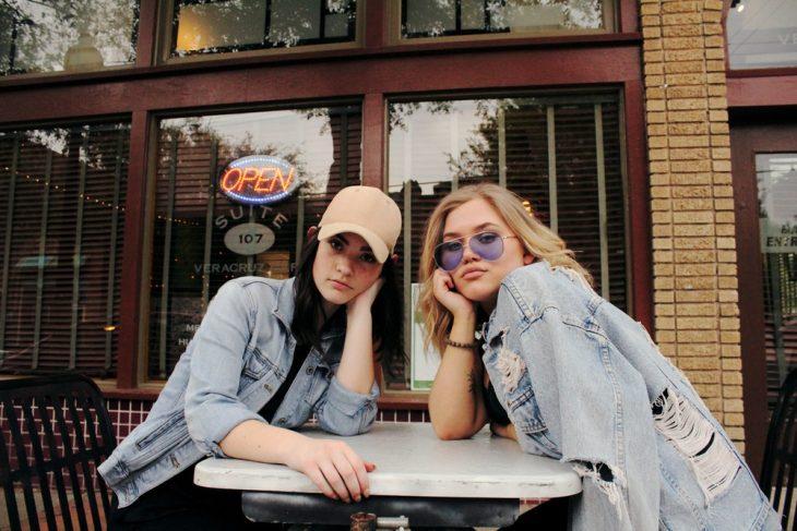 Tipo de amiga Tauro, chicas usando chamarras de mezclillas, sentadas en una mesa fuera de una cafetería, mientras charlan con sus rostros recargados en sus propias manos