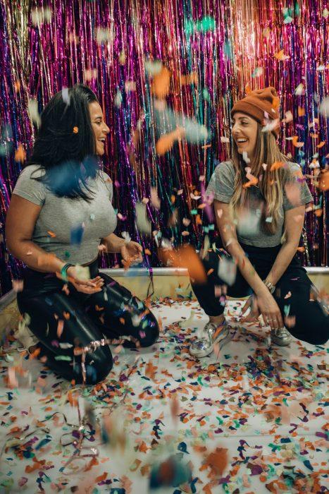 Tipo de amiga Leo, chicas inclinadas en cuclillas dentro de una habitación decorada con confeti y papel de colores