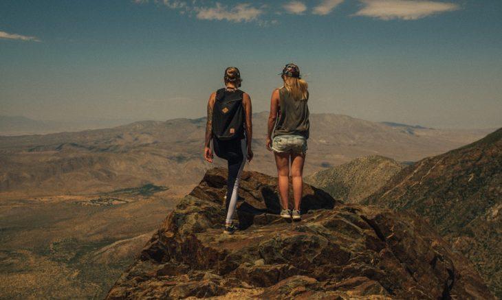 Tipo de amiga Geminis, amigas volteadas de espaladas, paradas sobre la cima de una montaña admirando el paisaje