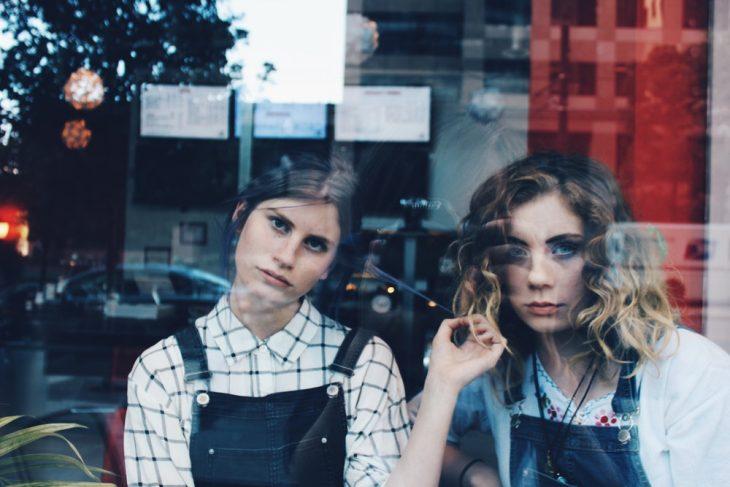 Tipo de amiga Libra, amigas llevando outfits iguales con overoles de mezclilla, mirando a atrvés de la ventana de una lavandería