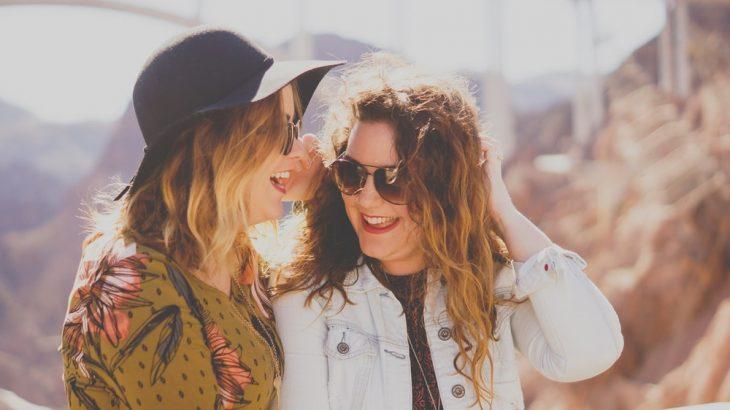 Tipo de amiga Sagitario, chica susurrándole al oído a su amigas mientras caminan por las calles soleadas