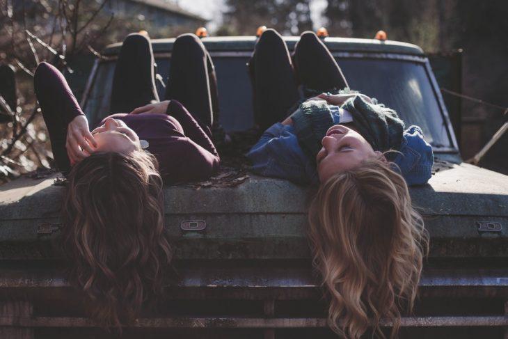 Tipo de amiga Escorpio, amigas recostadas boca arriba sobre el cofre de un automovil mientras charlan amenamente a mitad de carretera