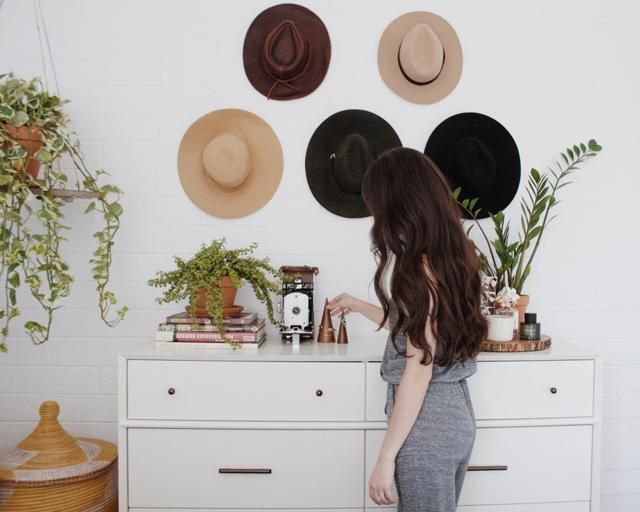 Mujer viendo sombreeros coldados en la pared como decoración