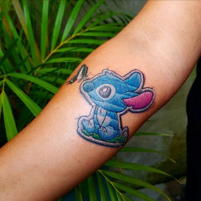 """Tatuaje de Lilo y Stitch bordado en el brazo, de tatuador brasileño Eduardo """"Duda"""" Lozano"""