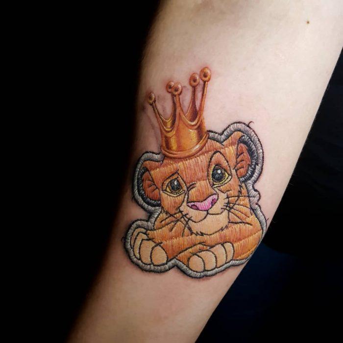 """Tatuaje bordado del Rey León de Disney en el brazo, de tatuador brasileño Eduardo """"Duda"""" Lozano"""