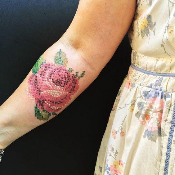 Chica mostrando su antebrazo tatuado con una rosa roja grande con efecto bordado en punto de cruz