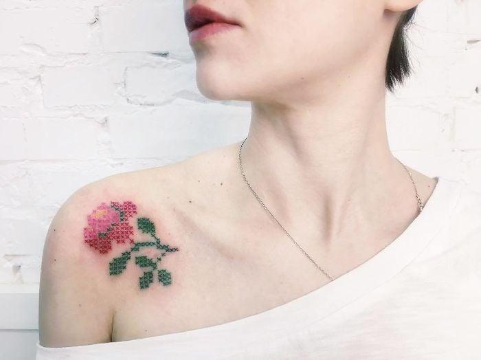 Mujer recargada en una pared blanca, mirando de lado, con el hombro descubierto para mostrar su tatuaje de rosa con efecto bordado en punto de cruz