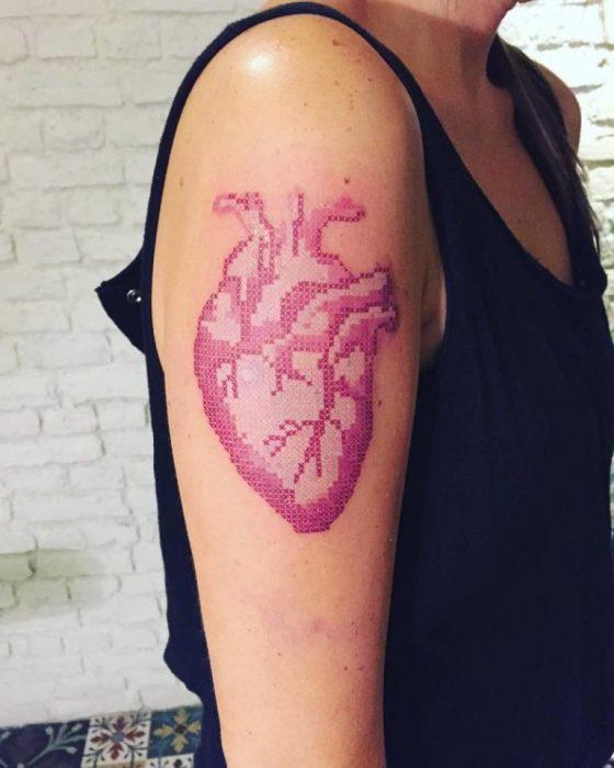 Persona delgada, mostrando el tatuaje de corazón con efecto bordado en punto de cruz que lleva en su brazo derecho