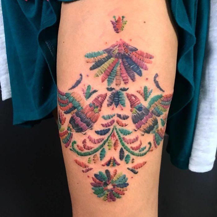 Tatuaje de aves de colores mirando al sol con efecto bordado