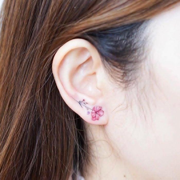 Tatuaje pequeño de una flor en el lóbulo de la oreja