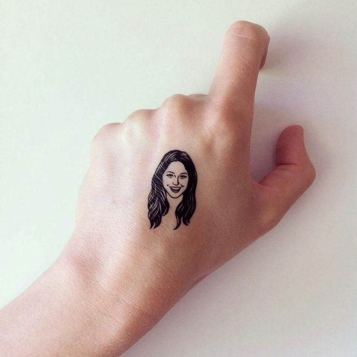 Mano con un tatuaje temporal de una chica sonriendo