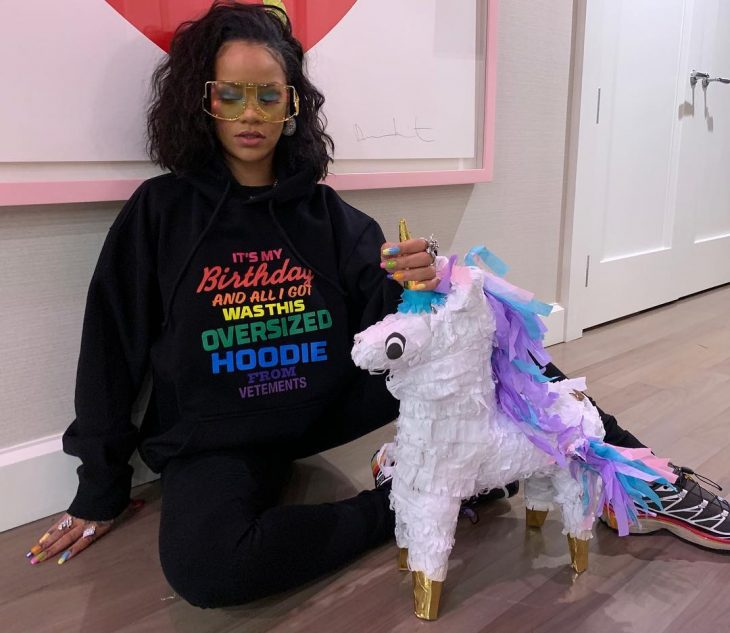Singer Rihanna dressed in big hoodie, black with rainbow-colored letters and a unicorn piñata, oversized trend