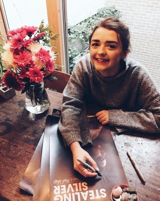 Actress Masie Williams of Game of Thrones signing autographs and smiling, dressed in a large woven sweater, oversized trend