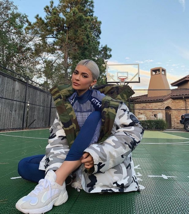 Kylie Jenner sitting on a basketball court, with gray hair, tennis and jacket with large military camouflage, oversized trend