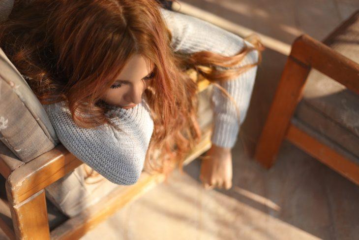 Chica con cabello largo, rojizo, llevando suéter azul cielo, recostada en un sofá de madera clara con cojines blancos, mirando hacia abajo, cansada y abatida