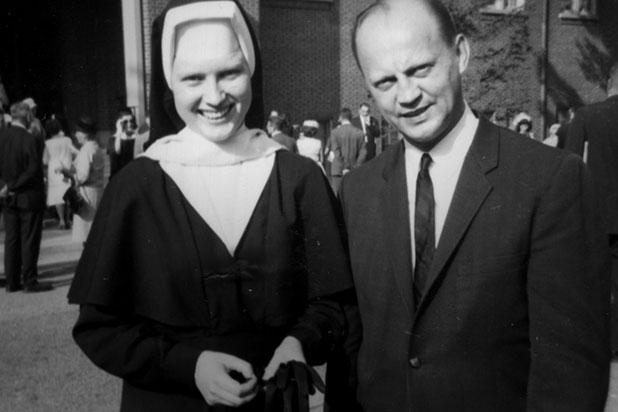 Monja usando hábito largo en color negro, con las manos entrelazadas, sonriendo, parada junto a un hombre que lleva traje sastre y sonríe para una foto, escena del documental The Keepers, Cathy Cesnik