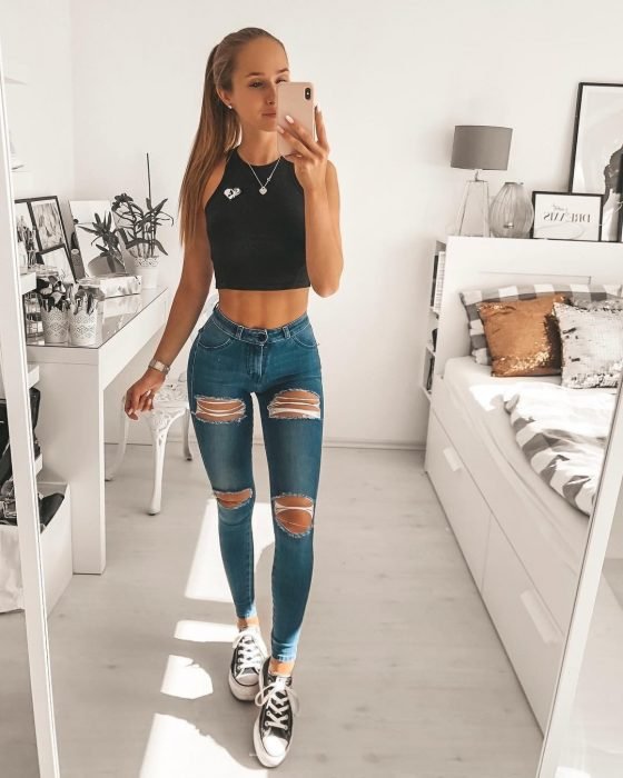 Chica rubia con jeans de mezclilla y top negro tomándose una fotografía con su celular
