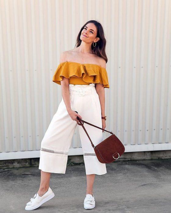 Chica modelando un pantalón holgado blanco con bodie de hombros caídos color amarillo con bolsa café
