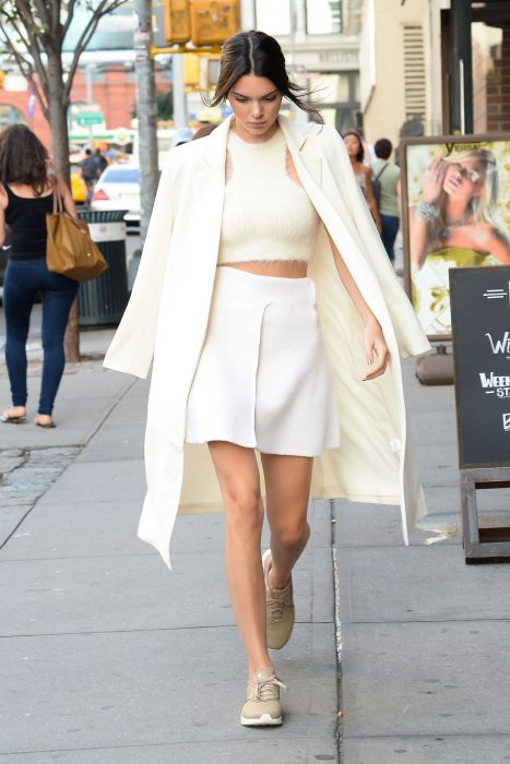 La modelo Kendall Jenner caminando por la calle con un conjunto de falda, crop top, saco de color blanco